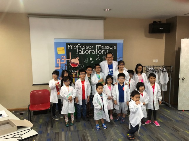 Children taking a photo with our science backdrop